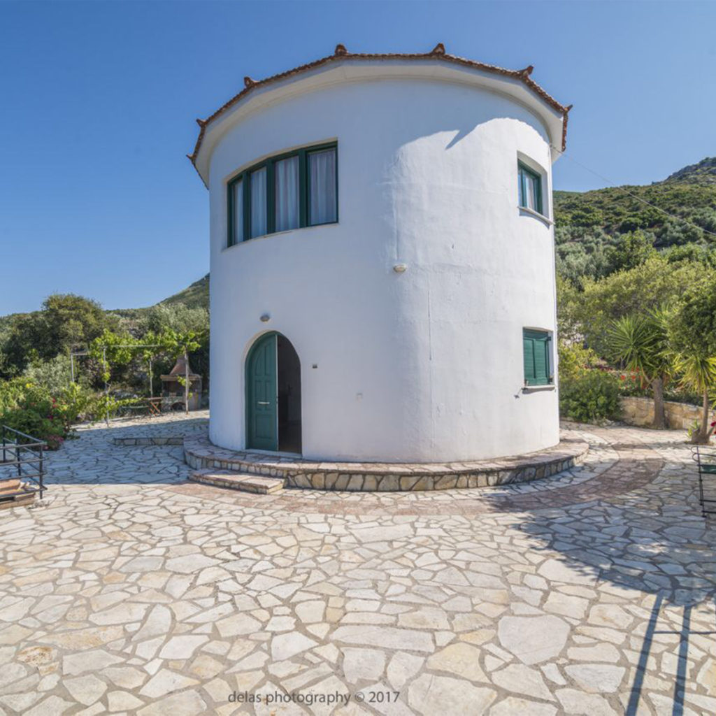 White painted circular building, Greek windmill converted into holiday accommodation, hills behind, stone terrace in front