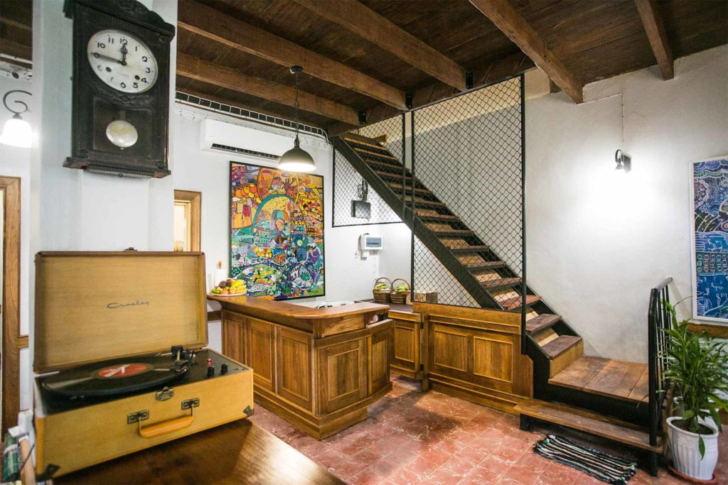 Room with wooden ladder-style stairs, beamed ceiling, quarry tiled floor, wood panelled kitchen area and and record player in wooden case.