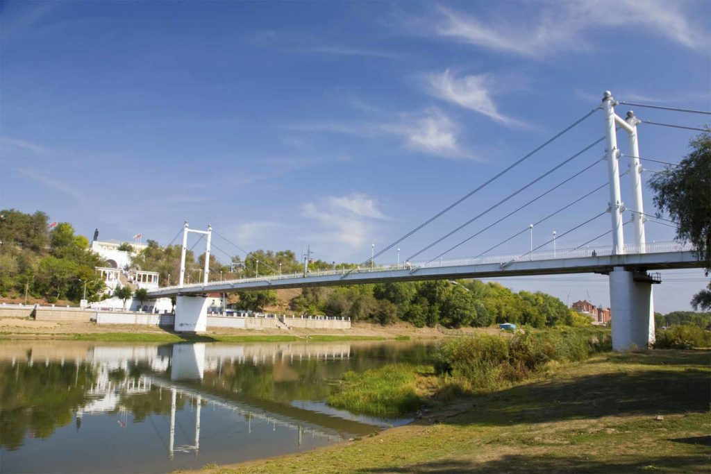 Modern suspension bridge over River Ural, perfect to explore on foot, scrubland and a building flying 2 flags