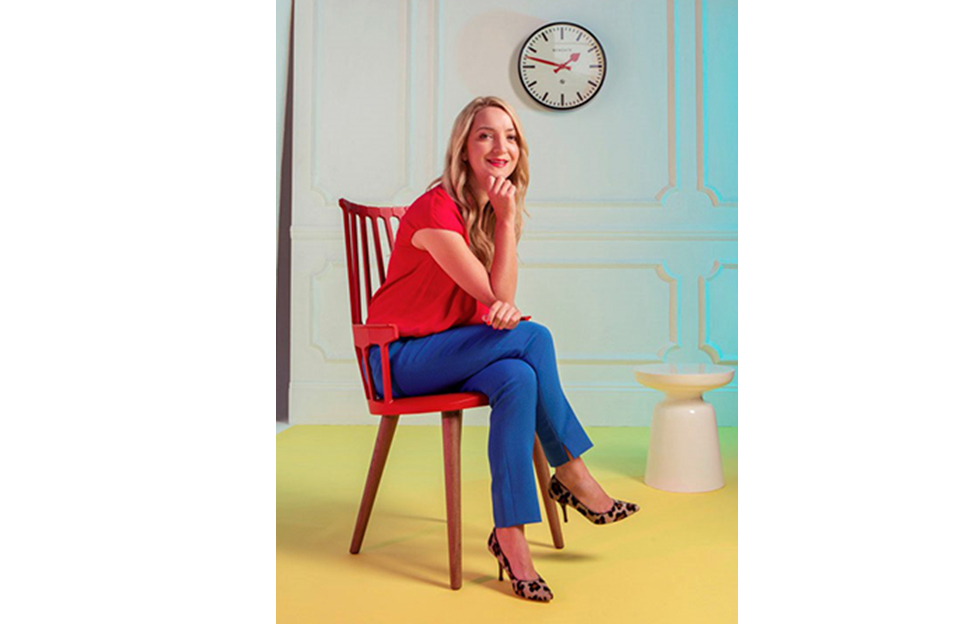 Author Caroline Corcoran shares writing tips. Caroline is young, slim, blonde, wearing red blouse and lipstick, blue jeans, sitting on a wooden chair leaning forward, chin on hand, smiling