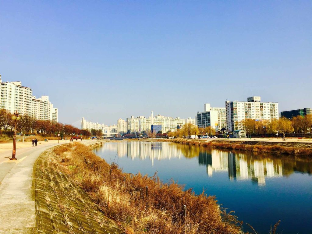 South Korea, Daegu. Still river, path alongside, white tower blocks in middle distance. A great place to explore on foot