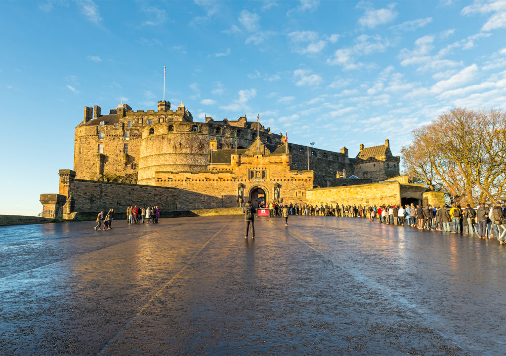 Edinburgh Castle from the Esplanade, golden stone against blue sky. A great city to explore on foot