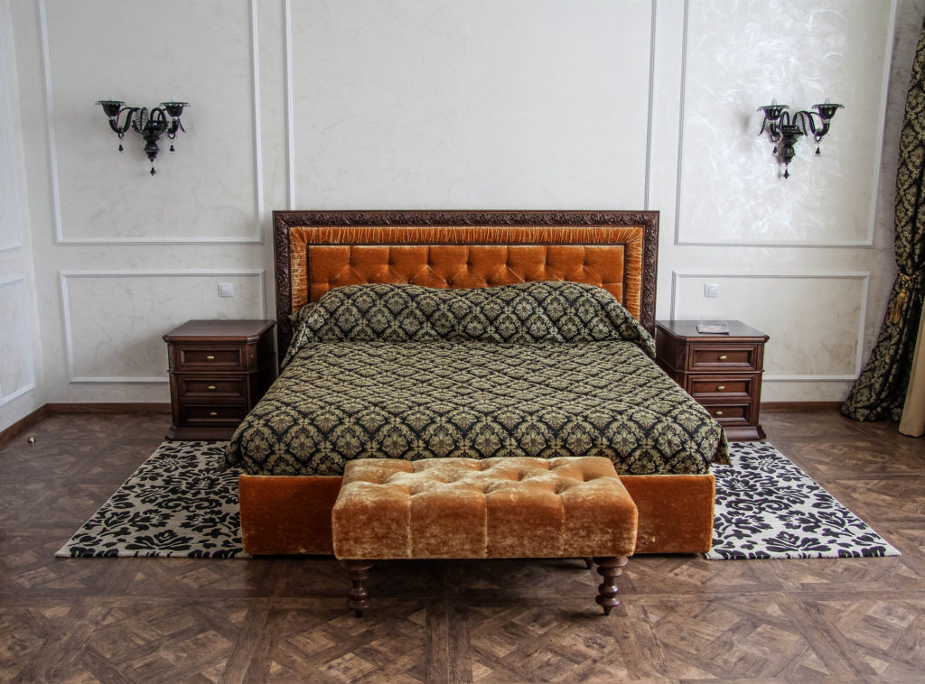 White panelled wall, parquet floor and sumptuous bed with rust-colouredvelvet headboard and footstool