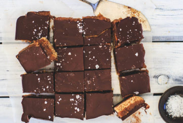 Millionaire's shortbread on baking paper, cut into 16 squares, one turned sideways to show biscuit, caramel and chocolate layers