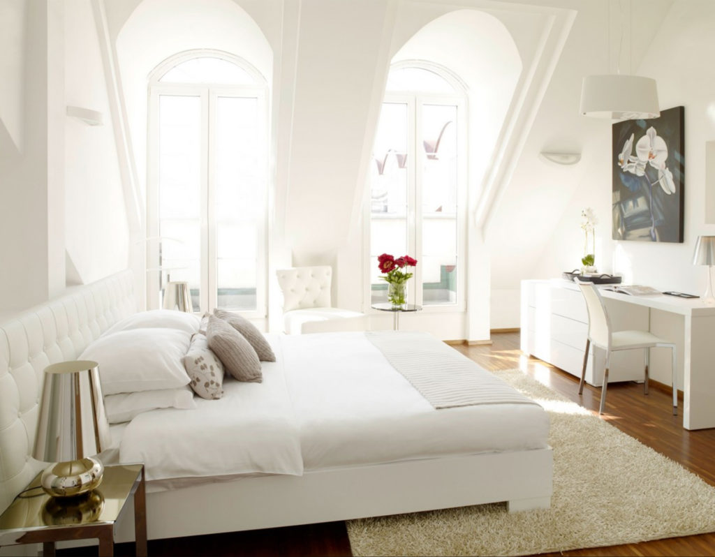 Completely white room with double bed and desk,light pouring through two high arched windows