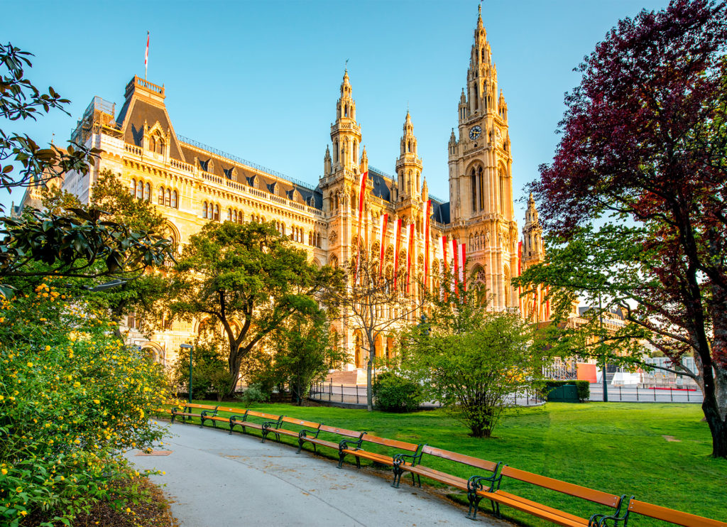 Beautiful Gothic style building bathed in golden light and draped in banners, trees in foreground