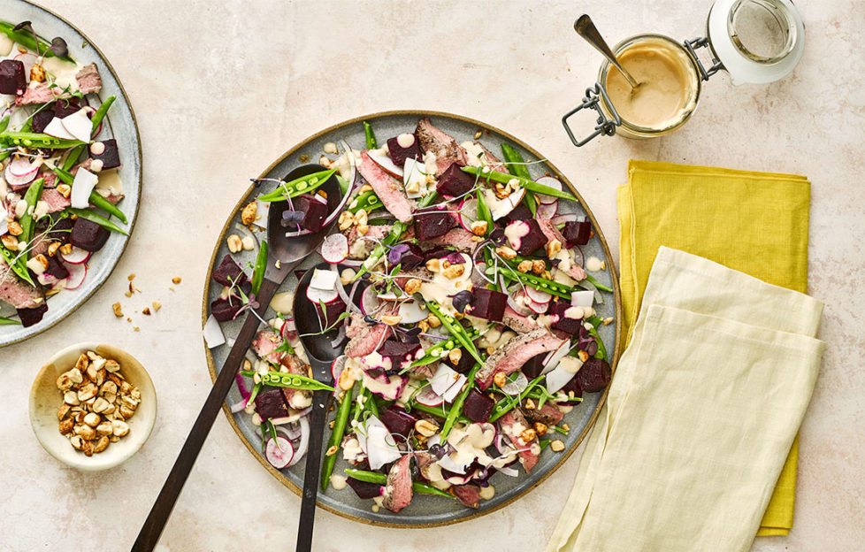 Large plate of colourful mixed salad, beetroot, sugar snaps and slices of steak, satay dressing in a dish at the side