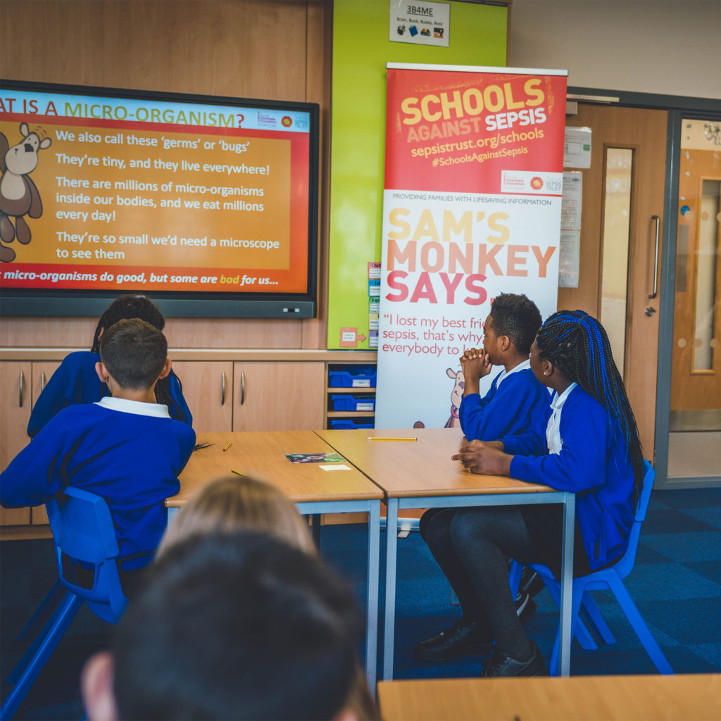 Pupils watching on-screen presentation on microbes, with pull up banner advertising sepsis awareness