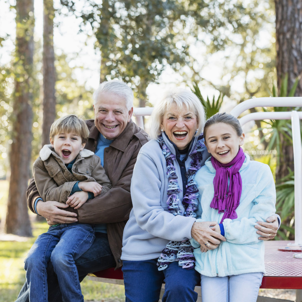 Elderly couple and two children aged 8-10 pose smiling in a rural play park