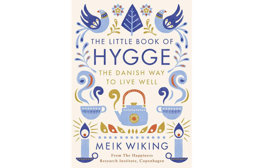 Cover of The Little Book Of Hygge, symmetrical patterns of blue birds, candles and steaming teacups