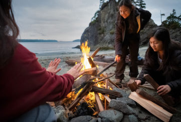 Three women around a campfire on a beach as dusk falls