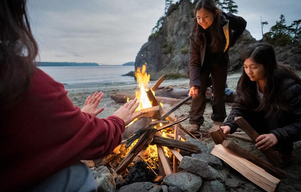 Three women around a campfire on a beach as dusk falls
