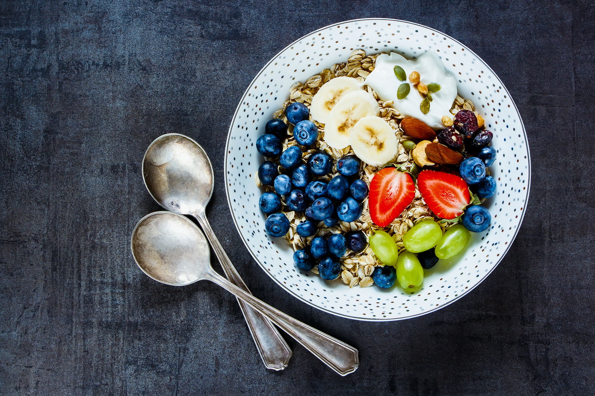 Plate of oat flakes, berries with yogurt and seeds for tasty breakfast on dark vintage background - Healthy food, Diet, Detox, Clean Eating or Vegetarian concept.