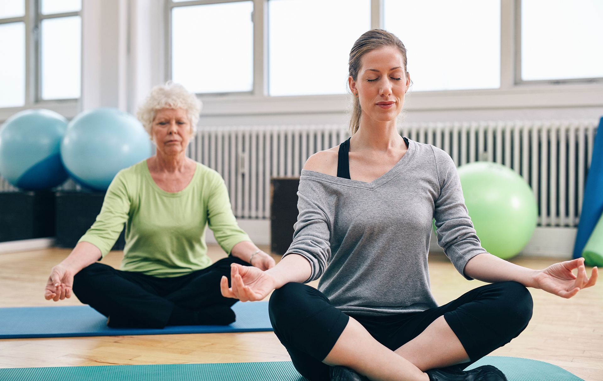 Two women practicing yoga in class. Female trainer and senior woman sitting in lotus position meditating.