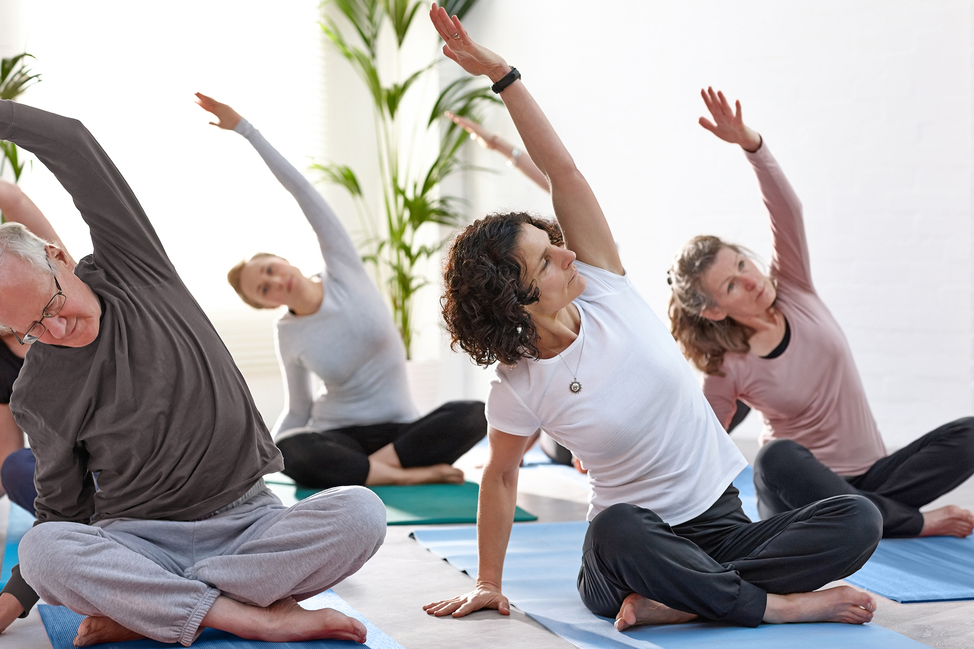 Group of mature people practising yoga at health club