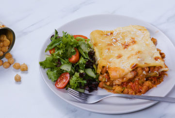 Vegetable lasagne with golden cheesy toppingon a plate with salad