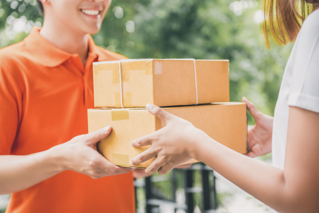 Man delivers two parcels to a woman at the door