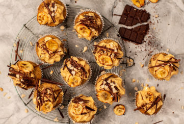 Peanut butter and banana vegan cupcakes on a cooling rack, decorated with icing, shards of dark chocolate and banana chips