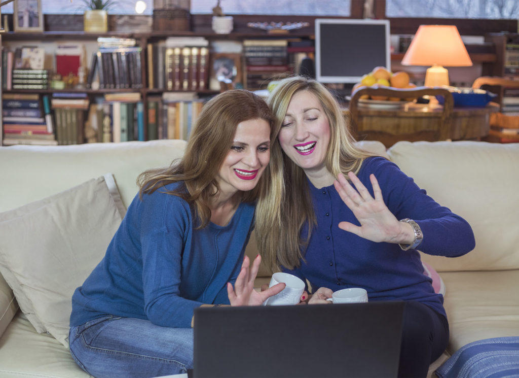 Two women on sofa waving at screen of laptop, talking to family on Skype