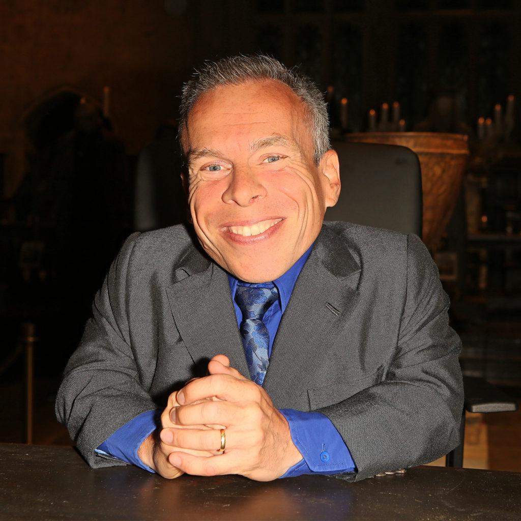 Actor Warwick Davies in jacket and tie, smiling