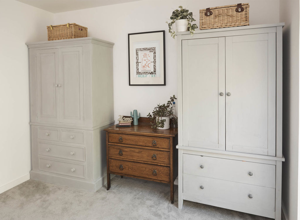 BHF makeover. 2 matching neutral painted wooden wardrobes, each with drawers in lower half,flank original drawers, 1 basket on top of each