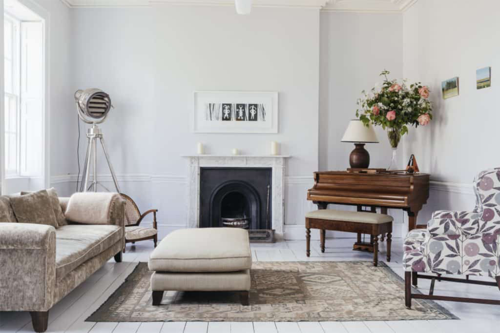 Simply decorated white room with black period fireplace, neutral sofas and piano, plus contemporary fan/heater/light in the corner