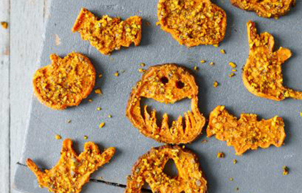 Tray of orange crispy sweet potato and pumpkin seed chews cut into bat and scary face shapes