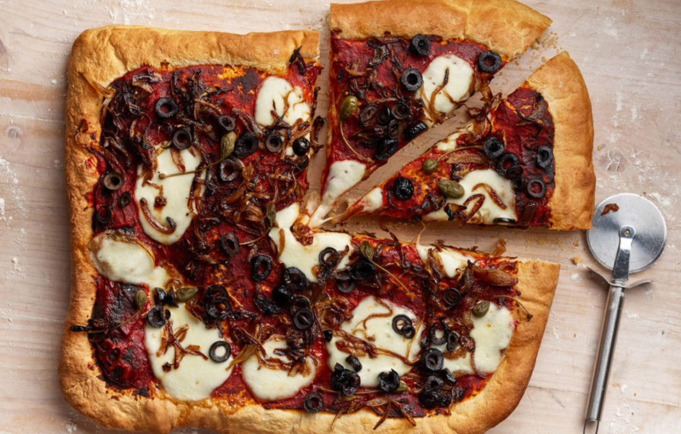 Rectangular home made pizza topped with white mozzarella slices, black ruby red tomato, sliced olives, strands of caramelised onion and capers, 2 slices cut