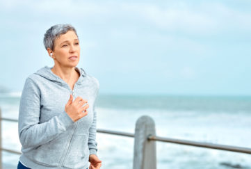 Shot of a mature woman listening to music while exercising outdoors