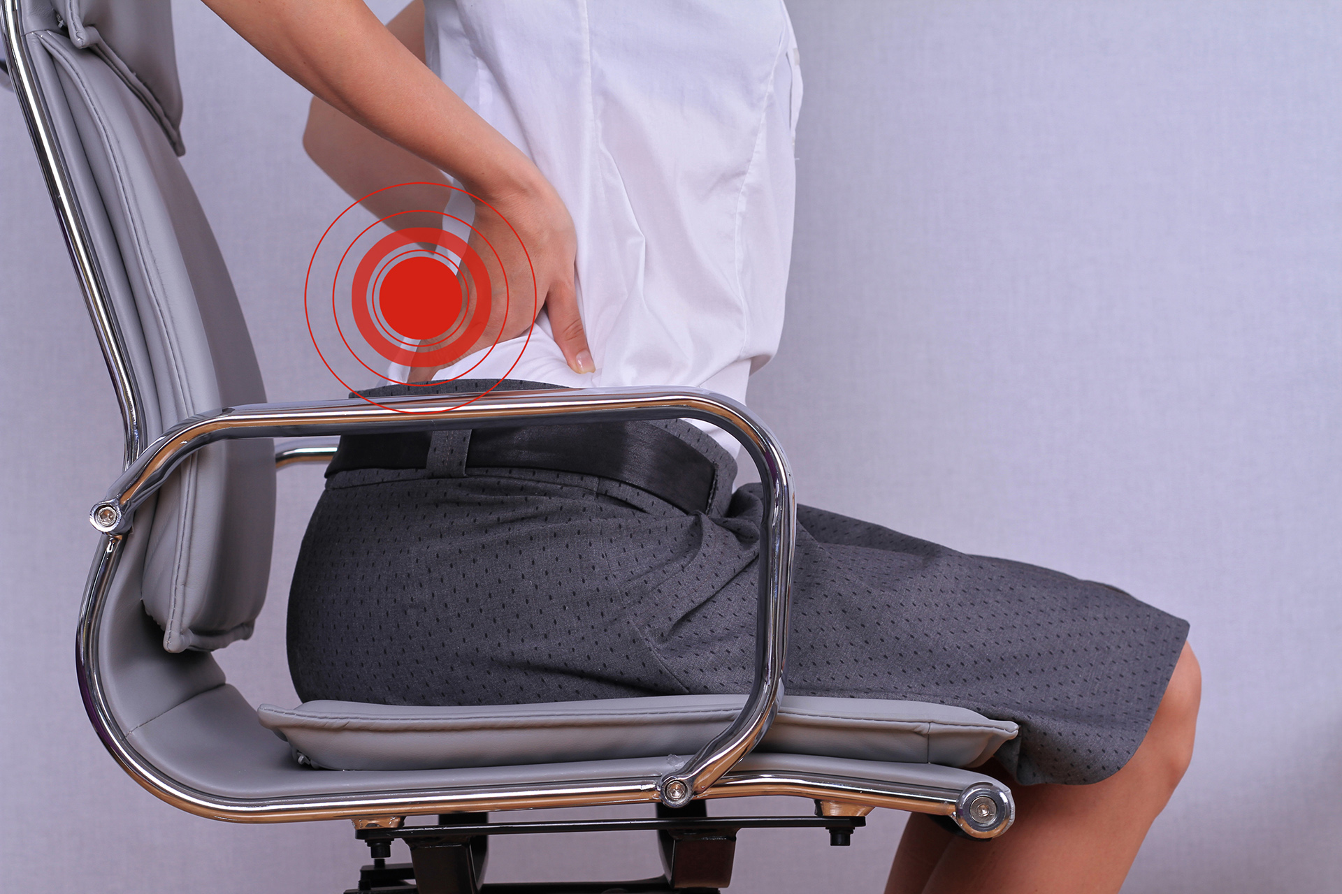 Business woman with back pain sitting in an office chair.