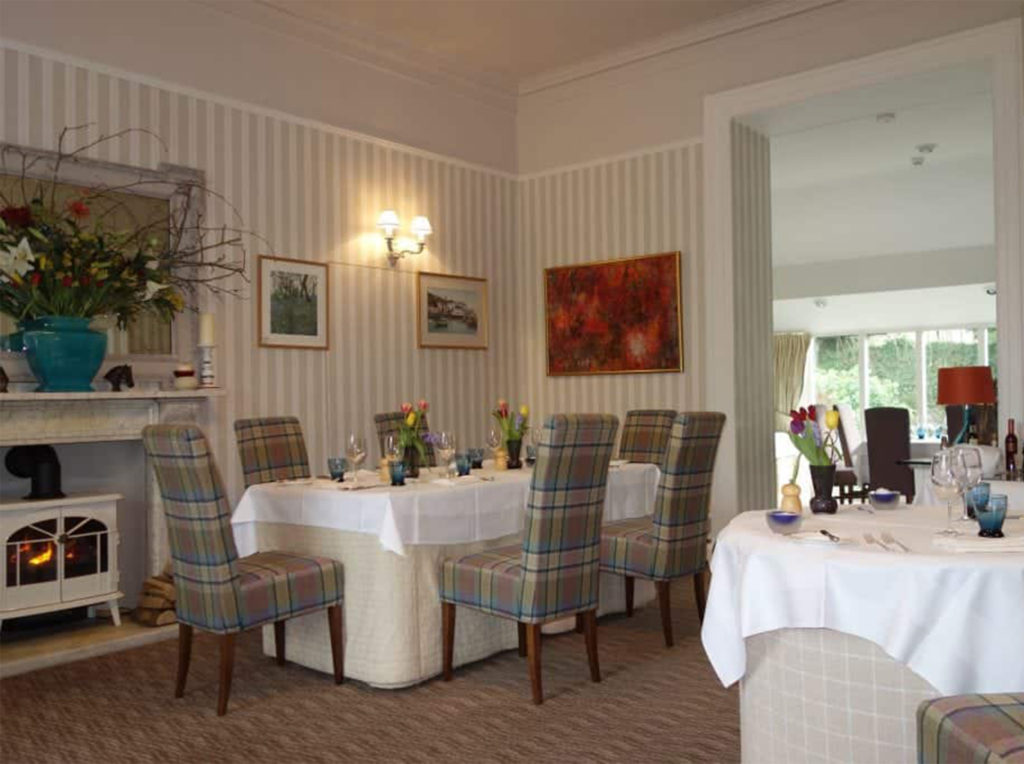Cosy hotel dining room, neutral theme, with tartan upholstered chairs and wood burning stove