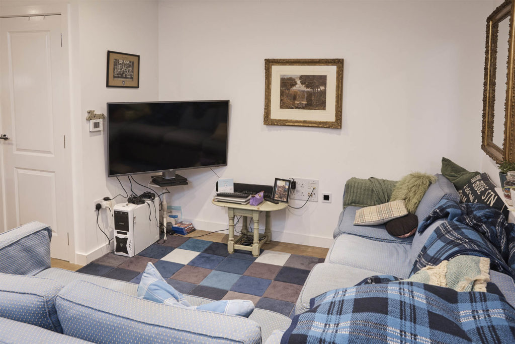 Lounge with TV, games drive, jumble of wires, L-shaped sofa with piles of throws and cushions