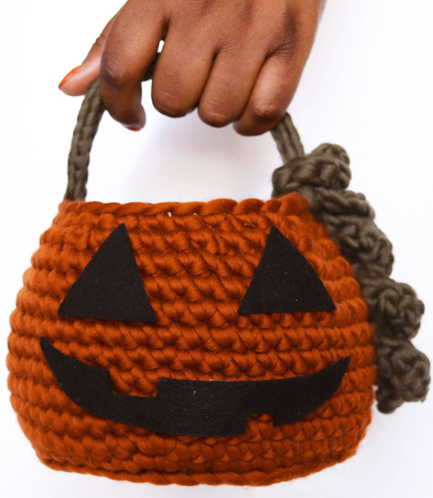 Person holding pumpkin basket by handle