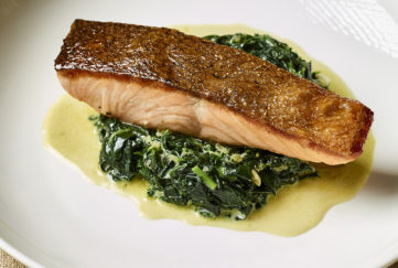 Pan fried salmon with crisp brown skin on bed of wilted spinach and watercress and melted butter jus