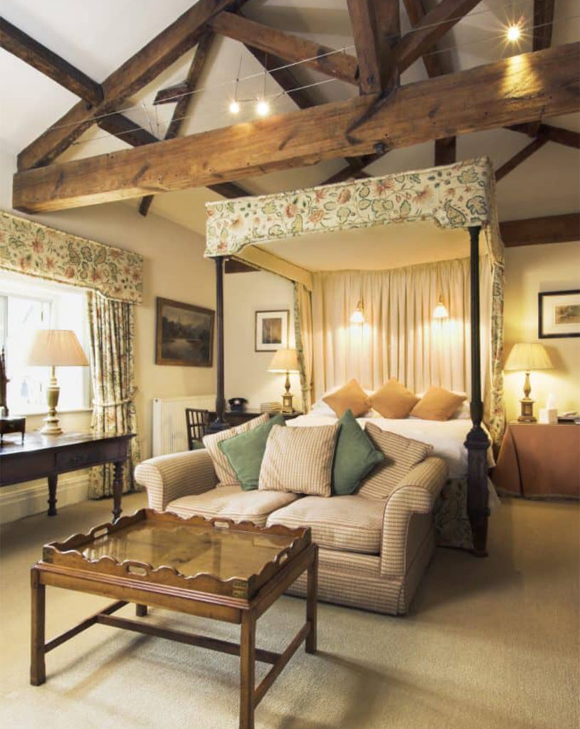 Exposed triangular roof beams and four poster bed