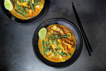 yellow thai curry in 2 black bowls, chopsticks on side, golden curry with green beans, fresh coriander and slice of lime