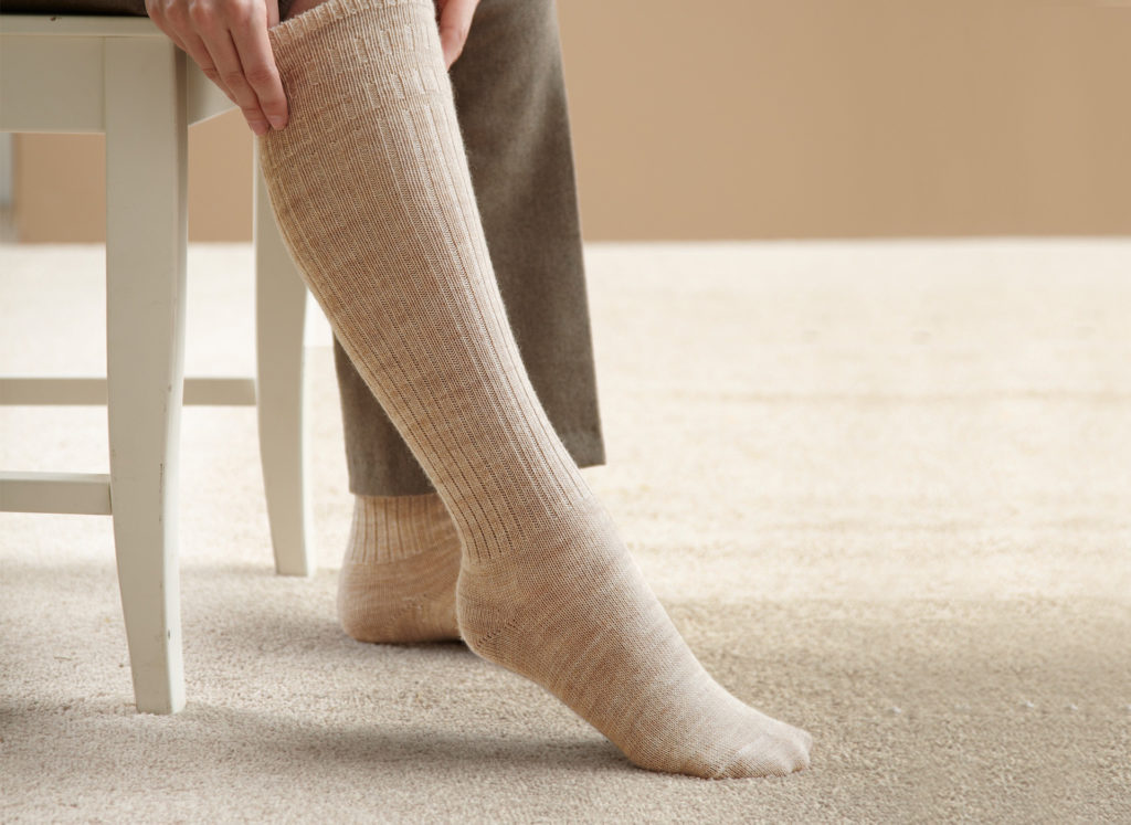 Woman pulling on pair of long beige socks