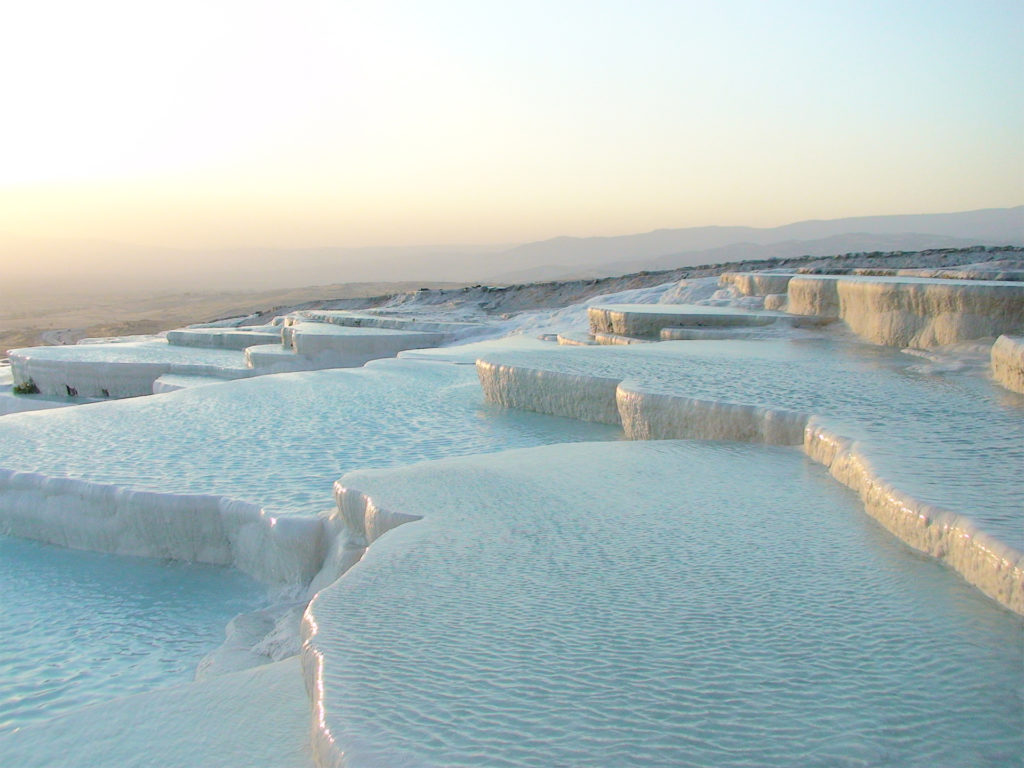 Water running gently over a series of rounded white terraces covered in mineral deposits, clear golden sky behind