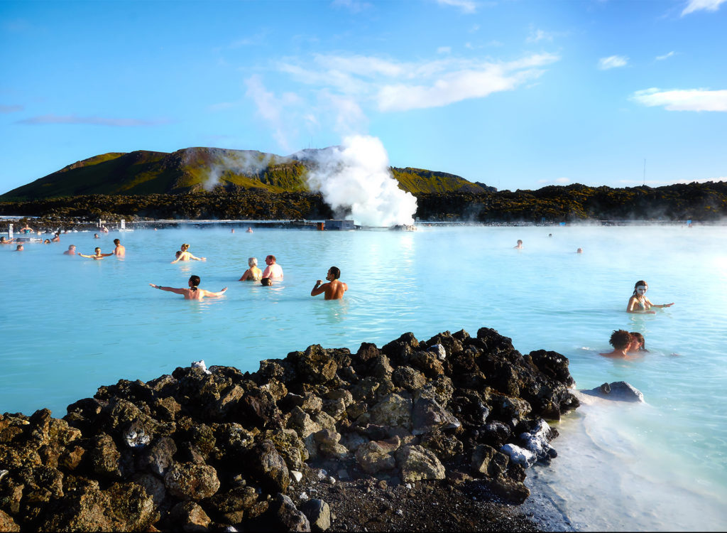 People bathing and playing in bright blue pool, rocks in foreground, hills and blue sky behind