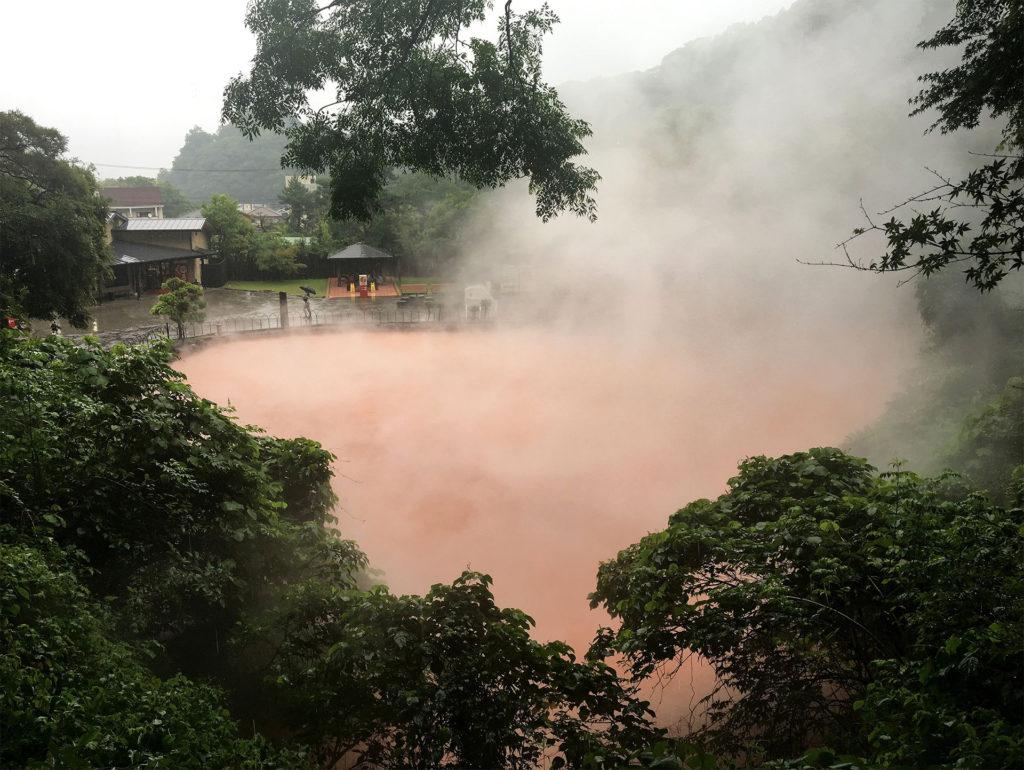 Reddish-brown steaming water seen through lush vegetation