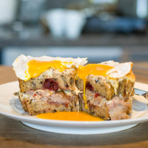 Toasted sandwich with turkey and cranberry, topped with soft fried egg, yolk dripping