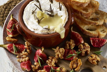 Melted Camembert cheese in dish, walnut halves, quartered fresh figs and rosemary sprigs