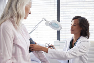 Woman Patient Having Blood Pressure Taken By Female Doctor In Office