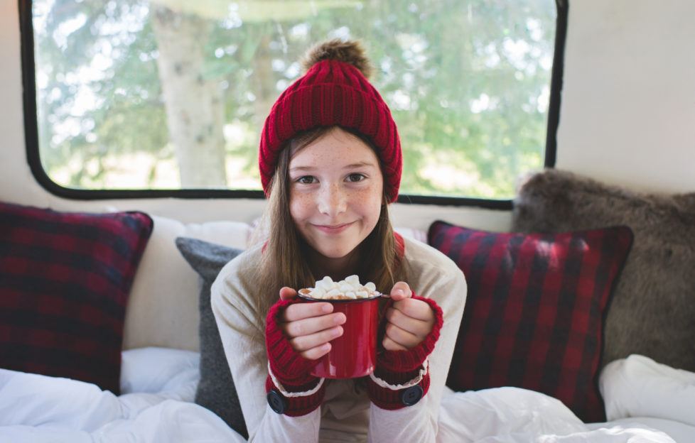 A young girl wearing warm clothing holds a warm beverage and smiles.