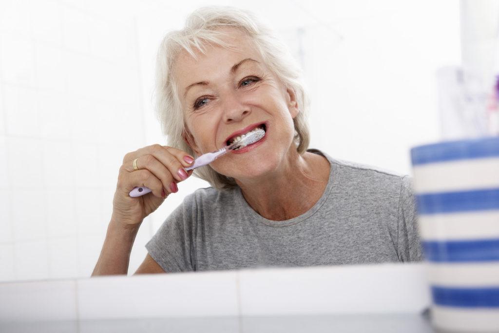 Senior Woman In Bathroom Brushing Teeth At Home