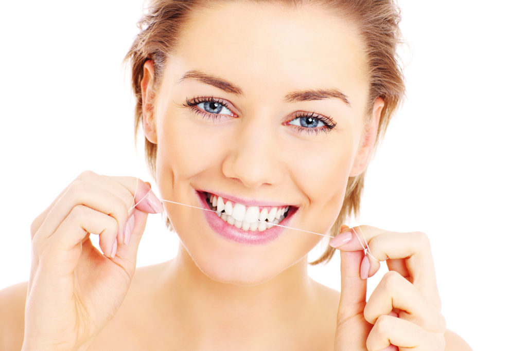 A picture of beautiful womanusing a floss for her teeth over white background