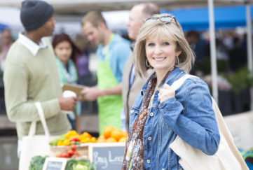 Happy senior woman shopping at outdoor farmers market for produce.