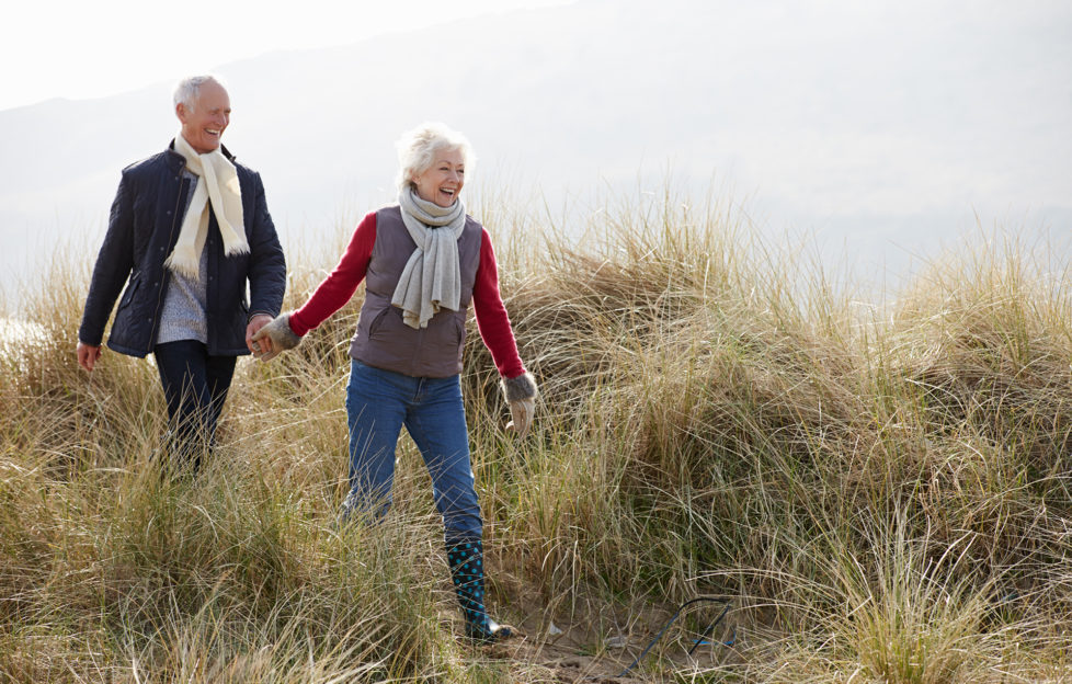 Senior Couple Walking Through Sand Dunes On Winter Beach Smiling