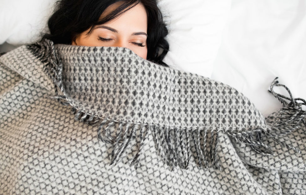 Half face of sleeping brunette under blanket