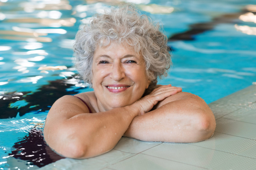 Portrait of elderly woman against the edge of a swimming pool and looking at camera. Fit and active senior woman enjoying retirement in the swimming pool. Beautiful mature woman relaxing in the swimming pool.